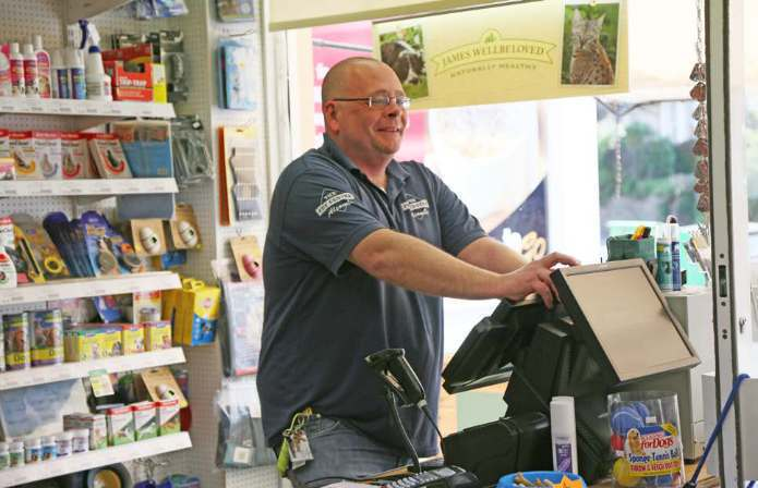 A man standing in front of a till at The Pet Centre